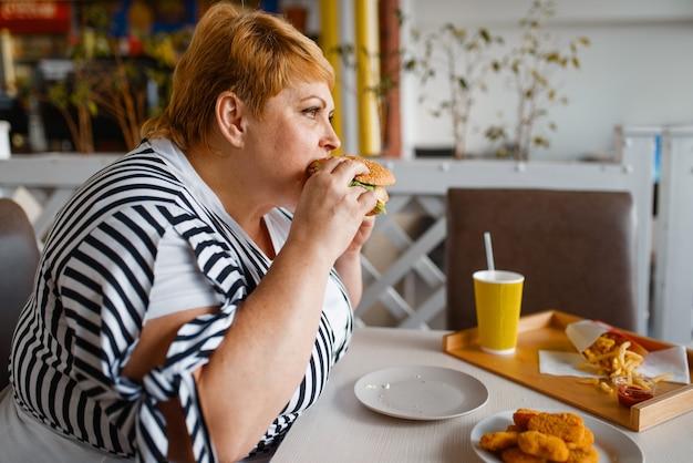 쇼핑몰 푸드 코트에서 햄버거를 먹는 뚱뚱한 여자.