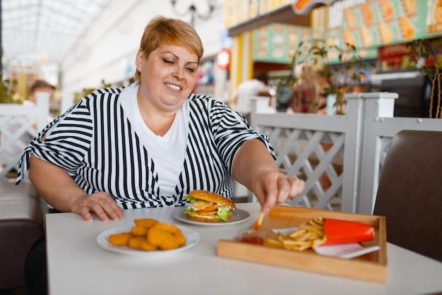 쇼핑몰 푸드 코트에서 감자 튀김을 먹는 뚱뚱한 여자.