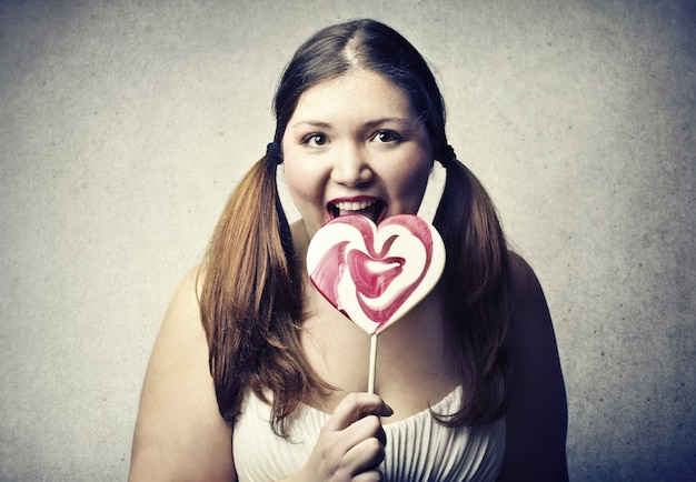Fat woman eating lollipop happily