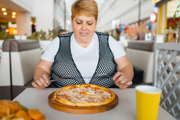 ファーストフードのレストランでピザを食べて太った女性。ジャンクディナー、肥満の問題でテーブルで太りすぎの女性人