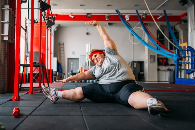 Толстая женщина упражнения на полу, тренировка в тренажерном зале
