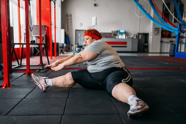 太った女性の床でのエクササイズ、ジムでのエクササイズ