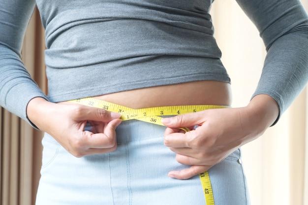 그녀의 배꼽 지방에 측정 테이프를 들고 뚱뚱한 여자 손. 여성 다이어트 라이프 스타일과 근육 개념을 구축합니다.