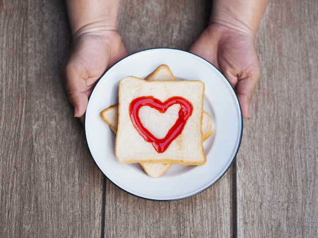 Fat woman hand holding plate of bread with red fruit jam heart shape