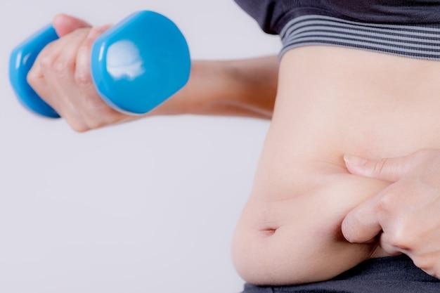 ダンベルを保持している太った女性。過度の腹脂肪を持っている太った女性の手。お腹を減らすヘルスケア。