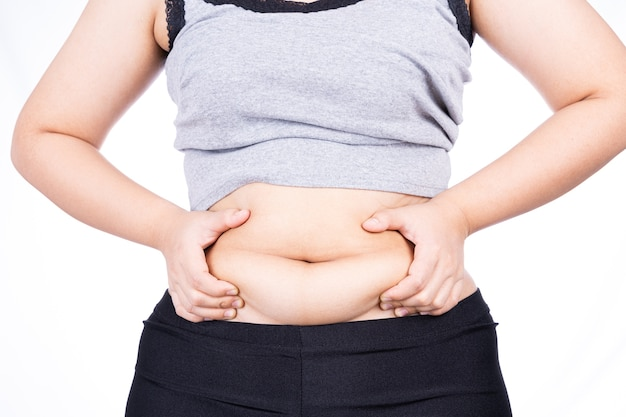 Fat woman holding excessive fat belly isolated