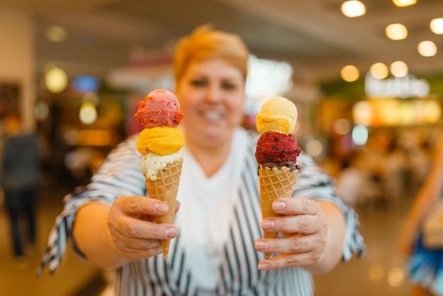 Толстая женщина, держащая мороженое в ресторане быстрого питания
