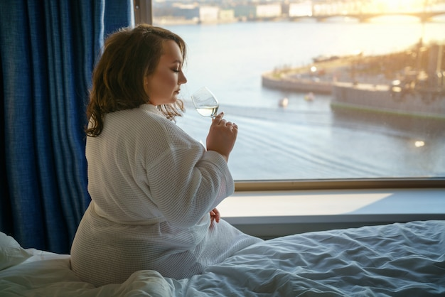 Fat woman looking out the window, the concept of excess weight