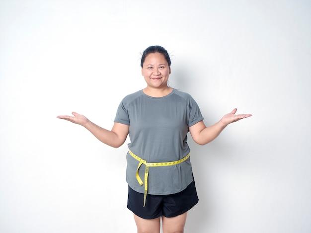 Толстая женщина измеряет талию с лентой на белом фоне и раскрывает руки