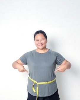 Толстая женщина измеряет талию с лентой на белом фоне, указывая на измерительную ленту