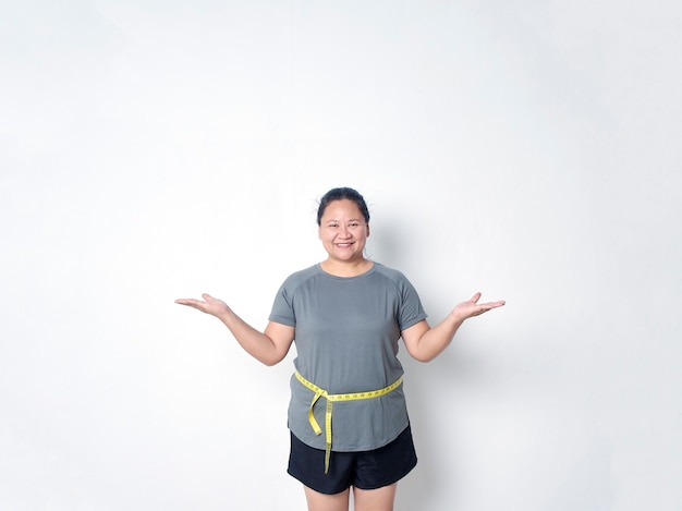 Fat woman measuring waist with tape on white background and her arms open