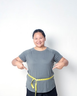 Fat woman measuring waist with tape on white background pointing to the measuring tape