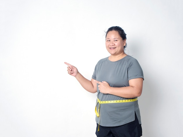 Fat woman measuring waist with tape on white background with copy space