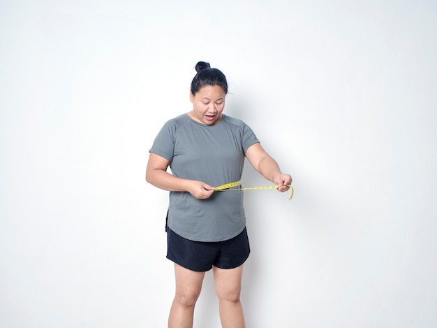 Fat woman measuring waist with tape on white background