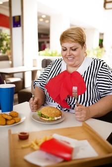 뚱뚱한 여자는 쇼핑몰 푸드 코트에서 패스트 푸드를 먹을 준비를합니다.
