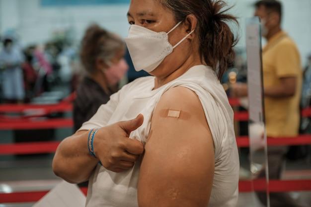 엄지손가락을 치켜드는 뚱뚱한 여성이 붕대로 코로나바이러스 코비드 어깨에 예방접종을 하러 갔다