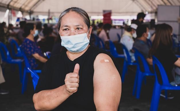 엄지손가락을 치켜드는 뚱뚱한 여성이 붕대로 코로나바이러스 covid19 어깨에 예방접종을 하러 갔다