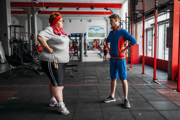 Fat woman talks with instructor after exercise with rope in gym.