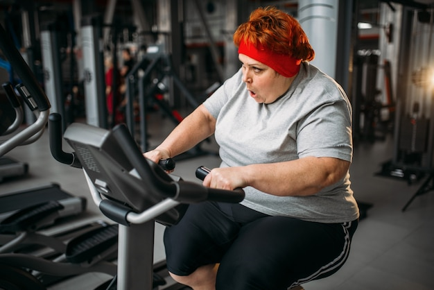 ジムでエアロバイクのトレーニングをしている太った女性。カロリー燃焼、スポーツクラブの肥満女性