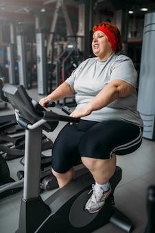 Толстая женщина тренируется на велотренажере в тренажерном зале