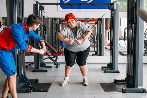 운동 기계를 사용하는 뚱뚱한 여자, 강사와 함께 훈련, 체육관에서 열심히 운동. 칼로리 연소, 스포츠 클럽의 비만 여성, 지방 연소