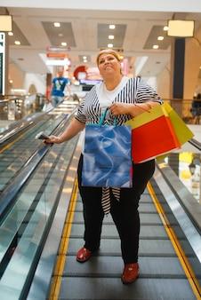 Толстая женщина с хозяйственными сумками на эскалаторе в торговом центре. женщина с избыточным весом в супермаркете, жирный шопоголик, проблема ожирения