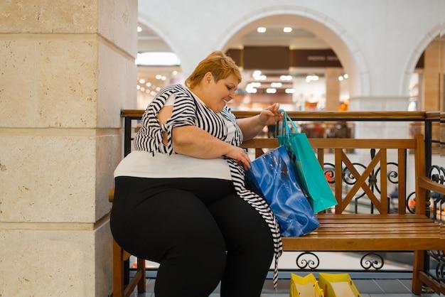 Толстая женщина с хозяйственными сумками, сидя на скамейке в торговом центре. человек женского пола с избыточным весом в супермаркете, проблема ожирения