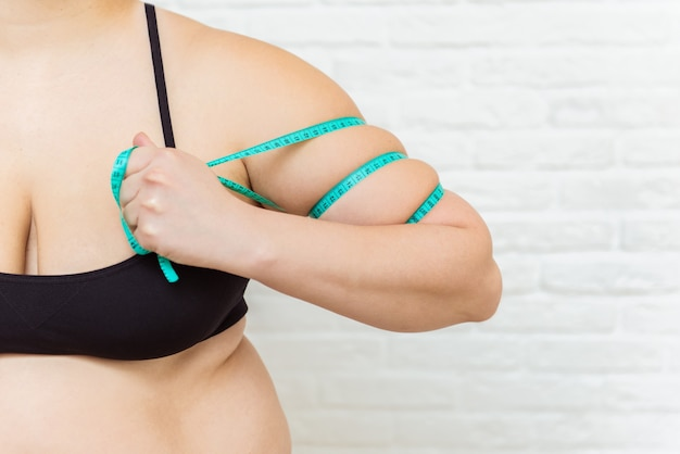 Fat woman, woman hand pinching on her excessive fat arm with measure tape, woman diet lifestyle concept