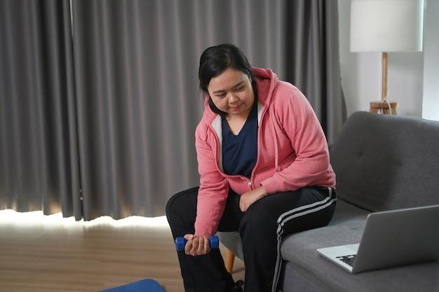 国内の家のソファでダンベルを使って太った女性のトレーニング。