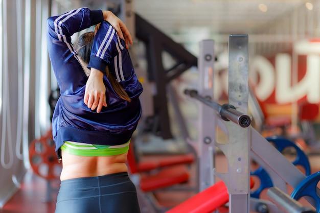 運動している太った女性。フィットネスと運動の前にジムで運動している若いフィットネス女性。