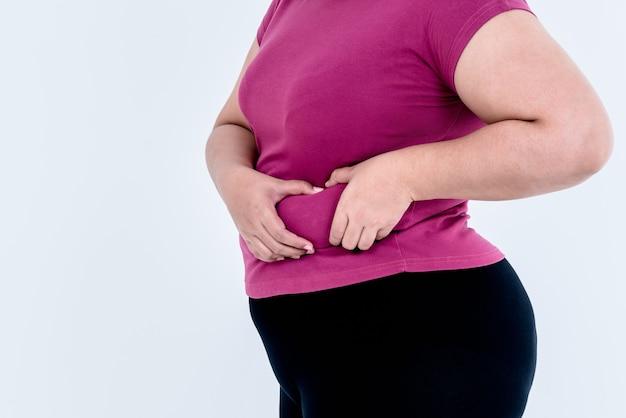 太った女性両手を使って余分な脂肪を腰の部分に保持する