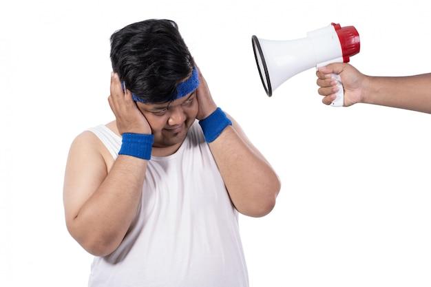 Толстый молодой человек закрыл уши руками