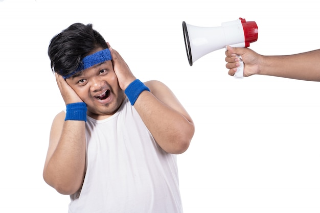 Толстый молодой человек счастливо закрывает уши руками