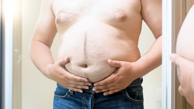 Fat young man standing at big mirror and holding his big fat belly. concept of male overweight, weight loss and dieting.