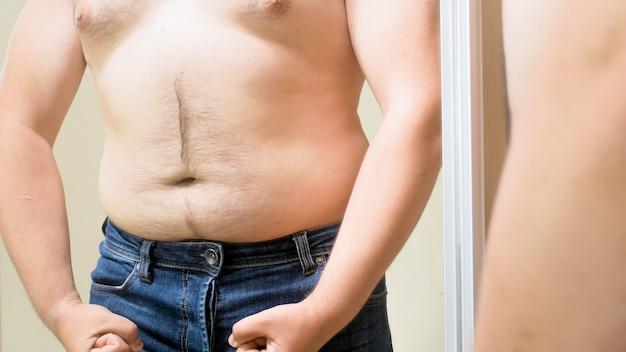筋肉質で体にフィットするふりをしている大きなお腹を持つ太った若い男。男性の太りすぎ、減量、ダイエットの概念。