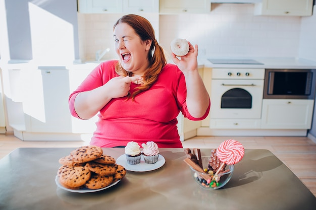 Fat young woman in kitchen sitting and eating sweet food. happy plus size model smile on camera and point on donut. daylight in kitchen. cookies and pancakes on table.