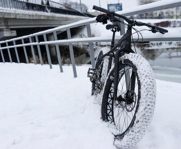 川の近くの雪の中のファットバイク