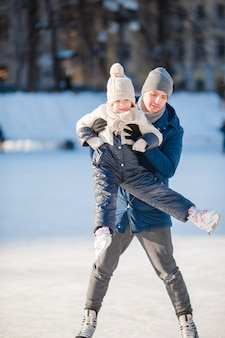 Father and adorable little girl having fun on skating rink outdoors