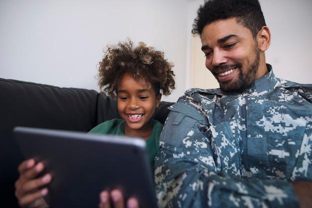 タブレットコンピューターで娘と一緒に漫画を楽しんで見ている家族と一緒に家にいる非番の兵士の父