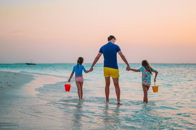 Отец и очаровательные маленькие дети на тропическом пляже, весело