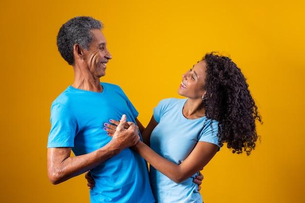 父と黄色の背景に笑みを浮かべてアフロ娘。父の日のコンセプト