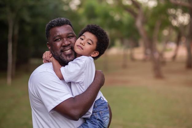 아버지와 아프리카 아들이 공원에서 서로를 안고 있습니다. 아버지의 날.