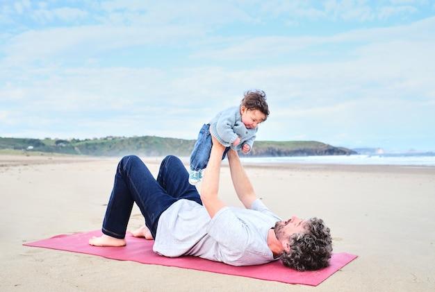 Отец и ребенок занимаются йогой на пляже