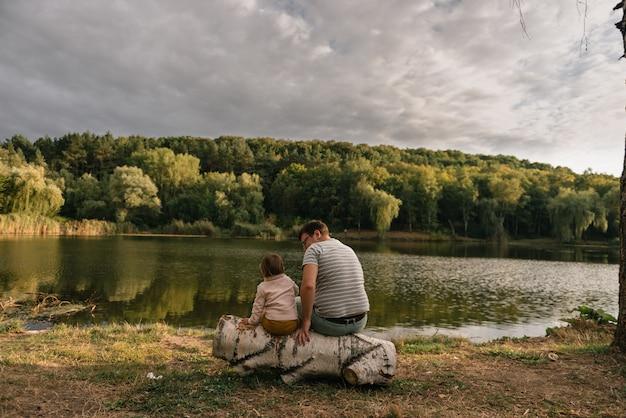 아버지와 딸이 호수 근처에 앉아입니다. 현지 여행. 새로운 정상적인 휴가. 아버지의 날