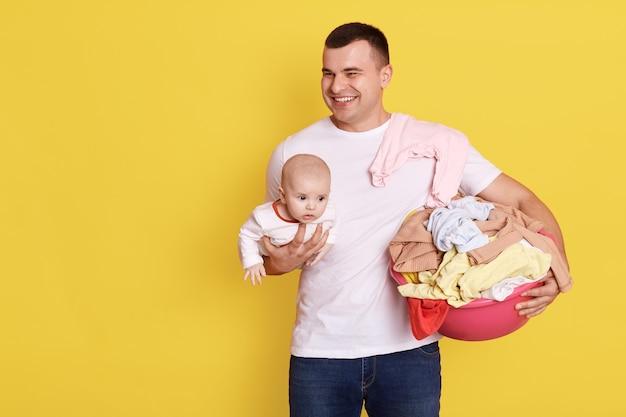 父と赤ちゃんは黄色い壁に隔離され、ハンサムな目をそらして笑い、洗濯後に生まれたばかりの子供と服を持って、幸せな表情の男性はカジュアルな白いtシャツを着ています。