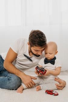 家で一緒に遊ぶ父と赤ちゃん