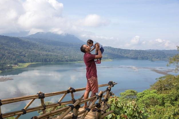 Отец и ребенок, стоя на скале с прекрасным видом