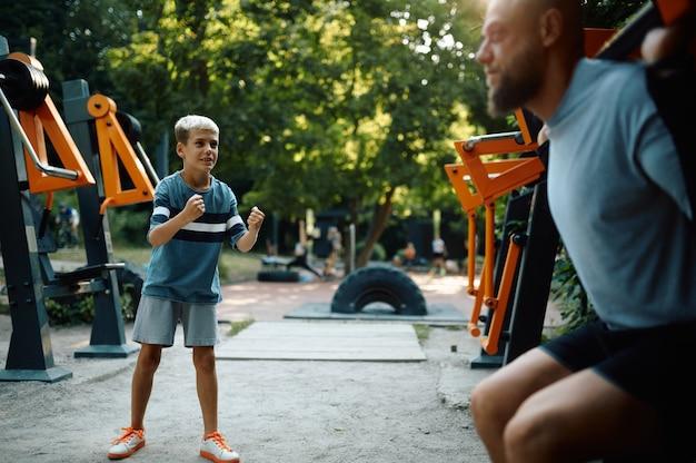 エクササイズマシンの父と少年、屋外の遊び場でのスポーツトレーニング。家族は夏の公園で健康的なライフスタイル、フィットネストレーニングをリードしています
