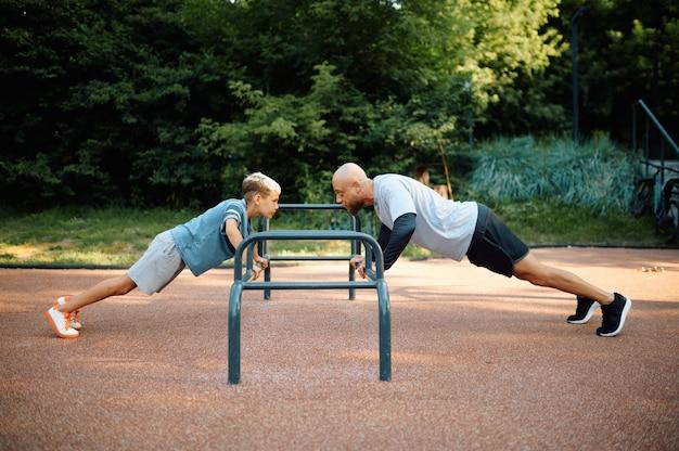 父と少年、腕立て伏せ運動、屋外の遊び場でのスポーツトレーニング。家族は夏の公園で健康的なライフスタイル、フィットネストレーニングをリードしています