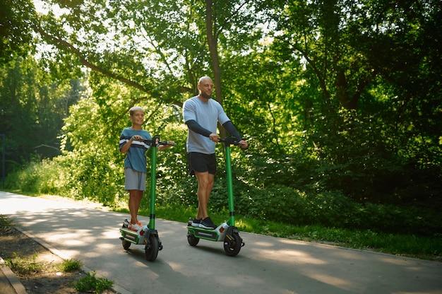 夏の公園でキックスクーターに乗っている父と少年。家族は健康的なライフスタイル、屋外でのアクティブなスポーツトレーニング、幸せな子供時代をリードしています
